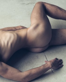 Nude man posing on the floor and on the chair