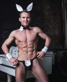 Muscle cock man in bunny suit near the piano