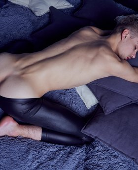 Gay leather twink posing on the bed