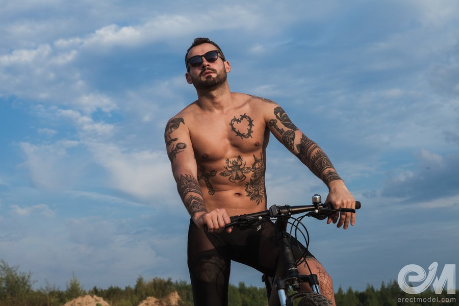 Fully tattooed man poses in see through cycling shorts