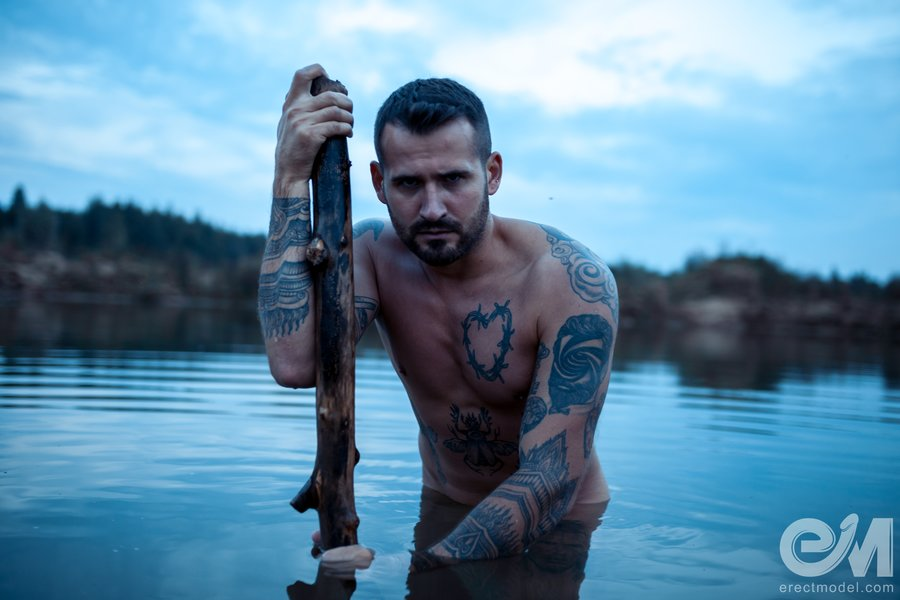 Naked man tattooed all over his body poses in the lake