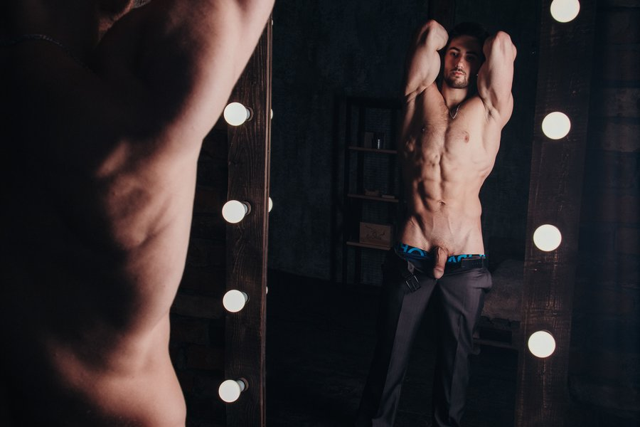 Sexy man undressing in front of the mirror