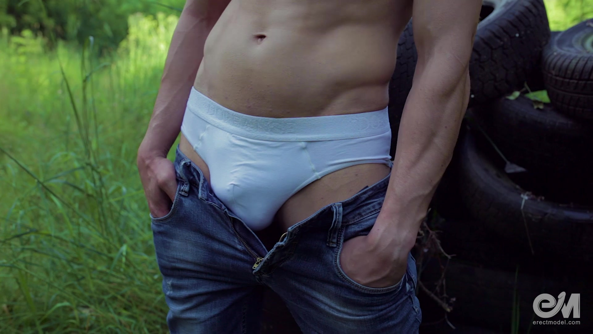 Sexy guy in jeans poses front and back outdoor