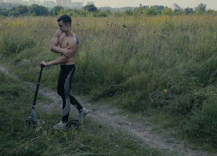 Teen muscle guy poses after riding a scooter
