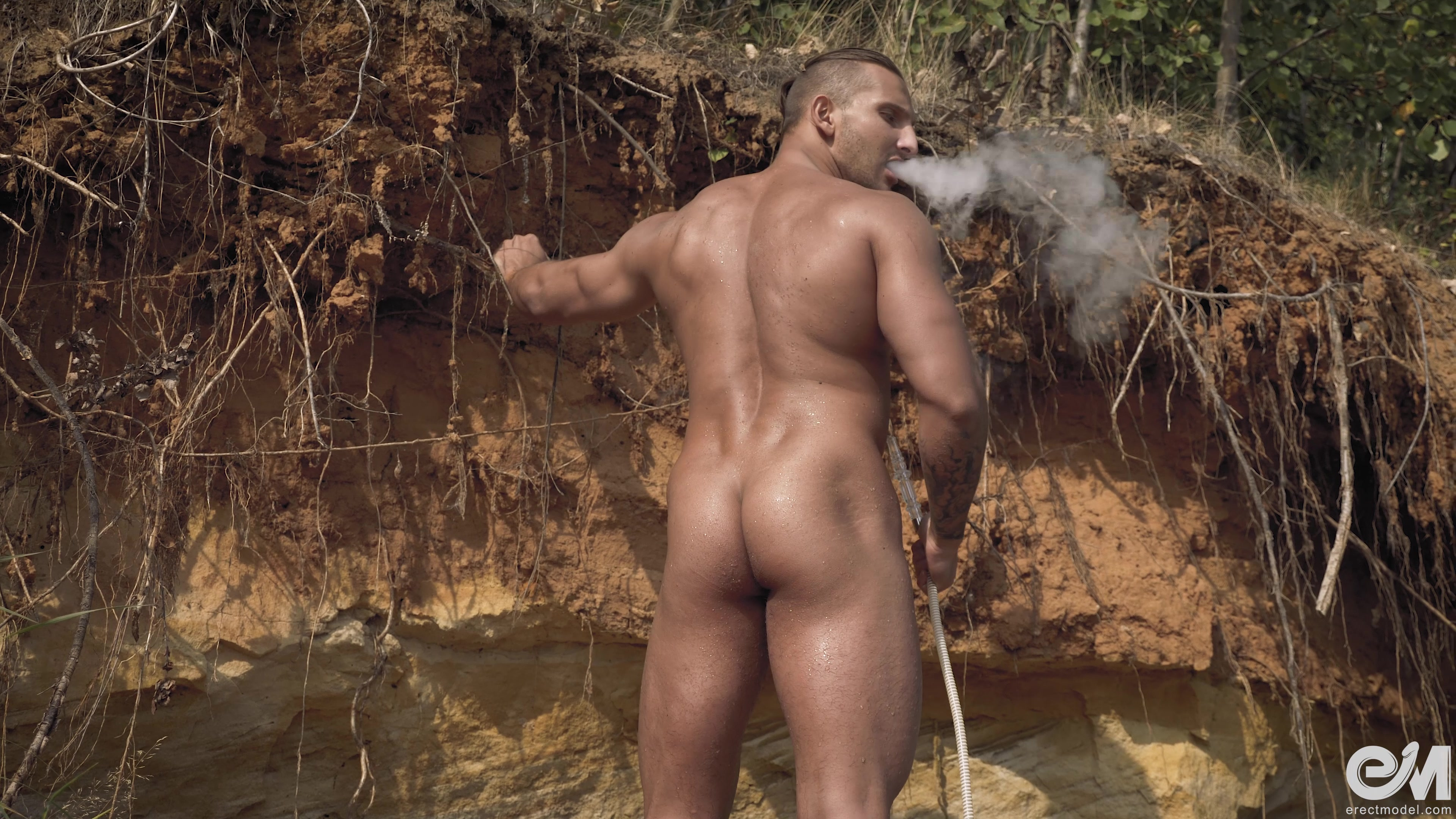 Muscle man smoking naked on the beach